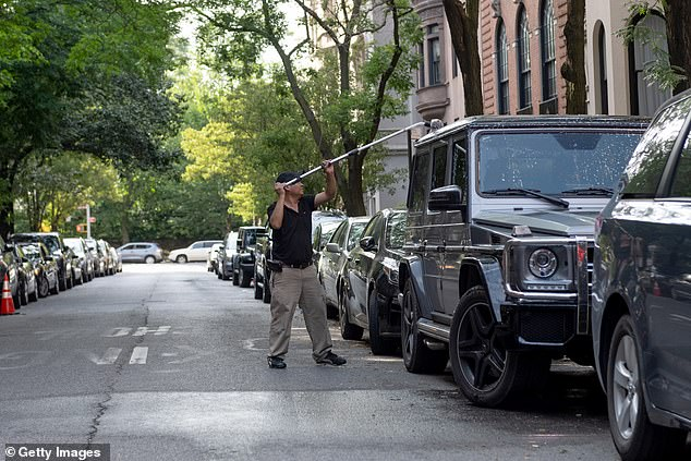 A man washes a Mercedes G- Class on a deserted street on Manhattan