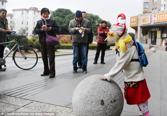Xiaoniu, wearing a Santa hat and rucksack, leans on a sculpture at Pudong Zhengdajiayuan housing estate